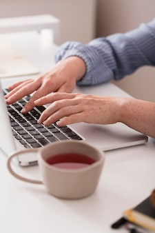 Profesora usando la computadora portátil para escribir durante la clase en línea y tomar el té