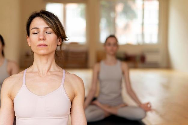 Profesora de yoga en clase enseñando asistentes