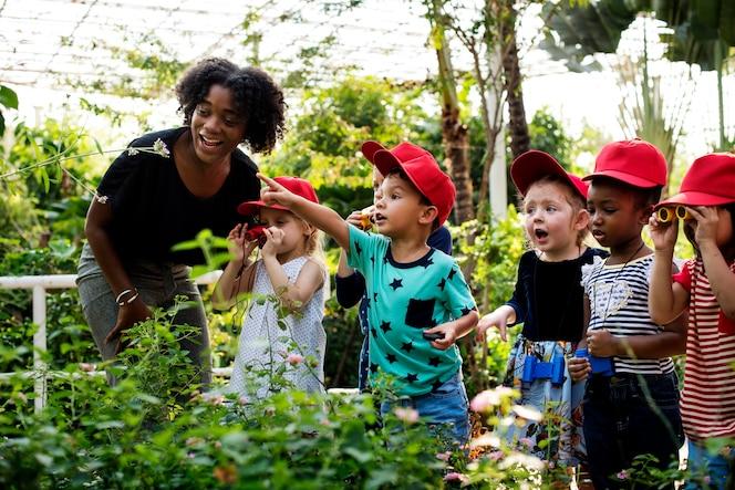 Profesores y niños escolares aprendiendo ecología jardinería