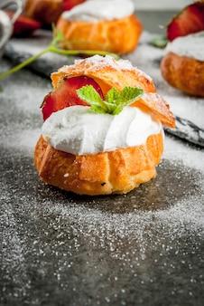 Profiteroles con crema batida, fresas y menta