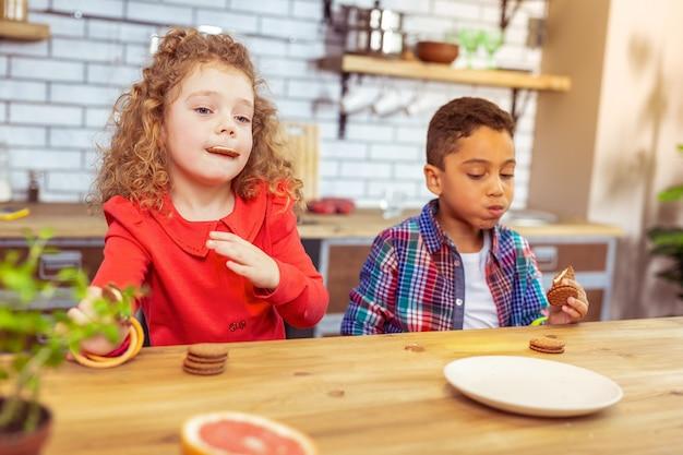 Profundamente en pensamientos. chico serio sentado a la mesa y comiendo galletas