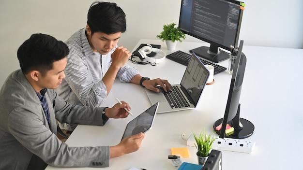 Un programador de dos hombres que trabaja con la computadora portátil y la codificación en la computadora.