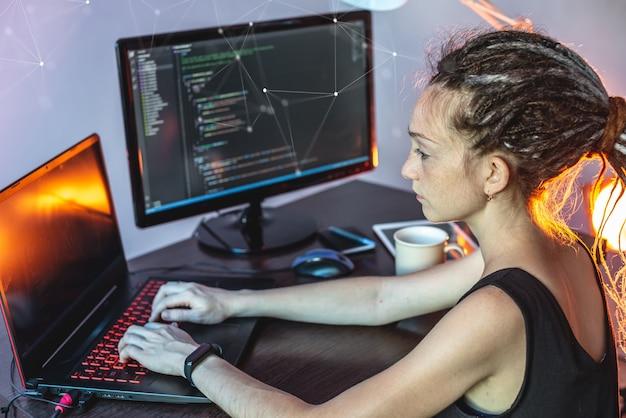 Programador femenino joven moderno está escribiendo código de programa en una computadora portátil en casa