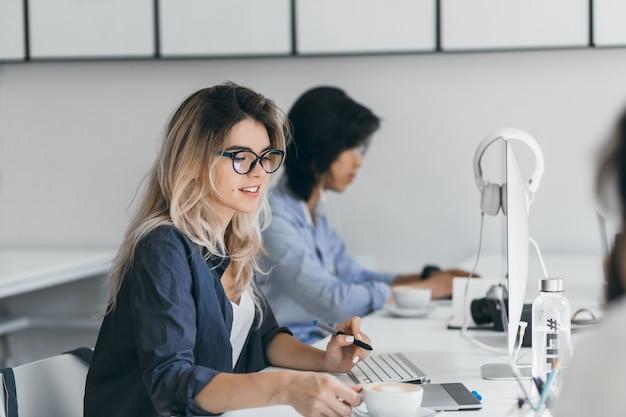 Programador femenino de pelo largo sosteniendo una taza de café relajante del trabajo. retrato de interior de un especialista europeo en ti sentado en el lugar de trabajo con una sonrisa junto a un joven asiático.