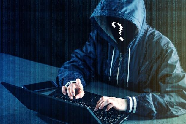 El programador de hackers anónimos utiliza una computadora portátil para hackear el sistema. robo de datos personales. infección de virus malicioso