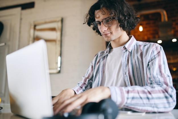 Programador informático experto joven en gafas escribiendo en la computadora portátil, código de prueba