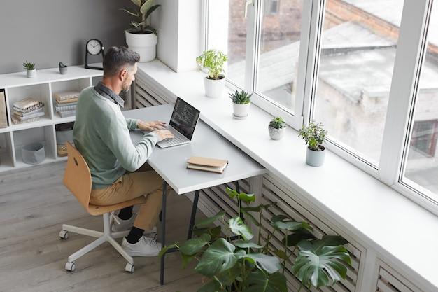 Programador informático sentado en su lugar de trabajo escribiendo en la computadora portátil en la oficina espaciosa