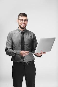Programador joven guapo con portátil en gris