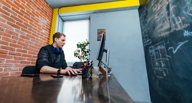 Programador masculino que trabaja en la computadora de escritorio cerca del monitor en la oficina en la empresa de desarrollo de software. tecnologías de programación y codificación de diseño de sitios web.