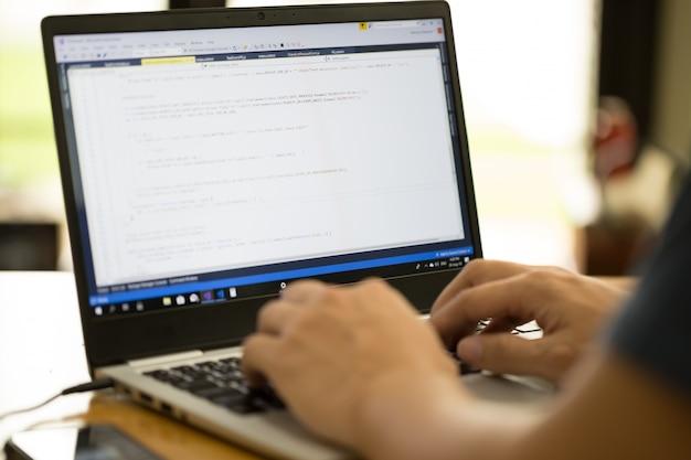 Programador o desarrollador independiente que trabaja en casa y escribe el código fuente con una computadora portátil
