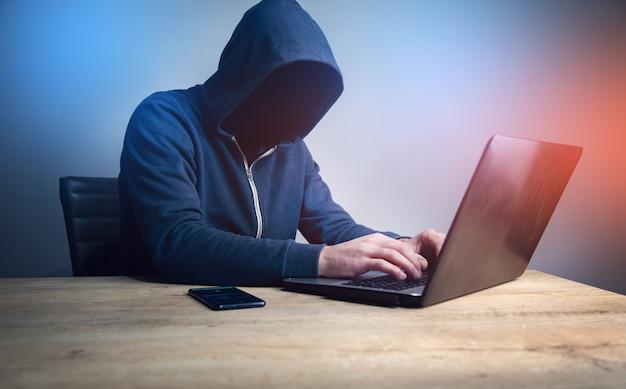 Programador o pirata informático escribiendo código en el teclado de la computadora portátil