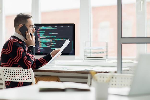 Programador ocupado hablando por teléfono con el cliente
