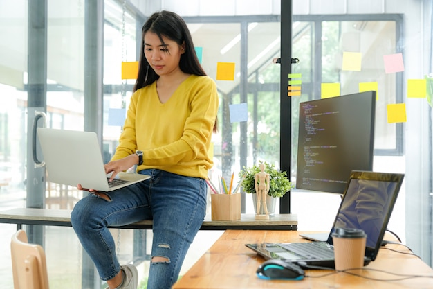 La programadora asiática usa una camisa amarilla, se sienta en los estantes y mira la pantalla del portátil en la pierna.