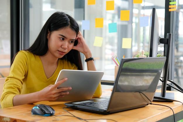 La programadora asiática usa camisas amarillas, mira la pantalla del portátil y sostiene una tableta. ella mostró una manera seria.