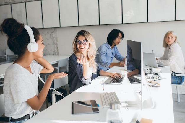 Programadoras web con estilo hablando sobre el trabajo mientras pasan tiempo en la oficina. retrato de interior de mujer africana en auriculares y trabajador asiático usando computadoras.