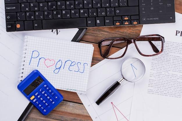 Progreso en el bloc de notas y varios documentos comerciales sobre fondo marrón