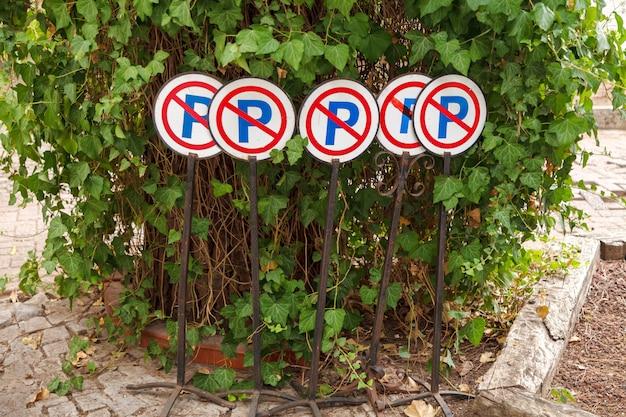 Se prohíben las señales de tráfico. aparcamiento en un arbusto verde