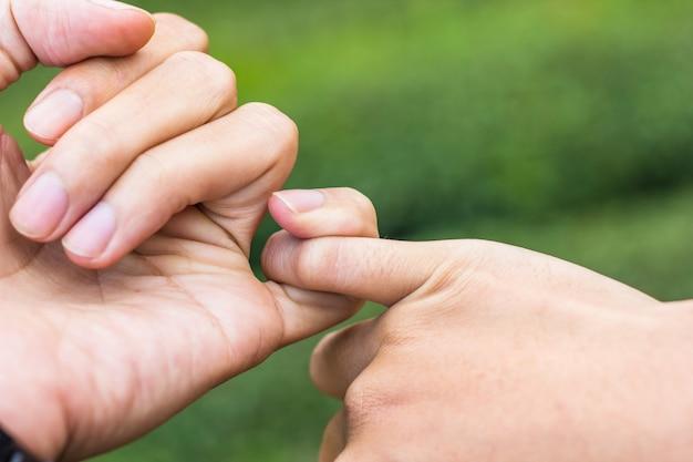 Promesa de concepto ciérrese encima de las manos de la pareja que se enganchan el dedo índice de cada uno junto.