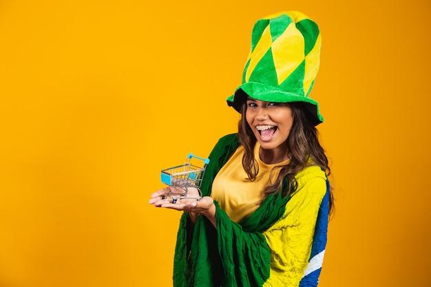 Promoción de fútbol. mujer sosteniendo un mini carrito de compras en manos vistiendo ropa brasileña.