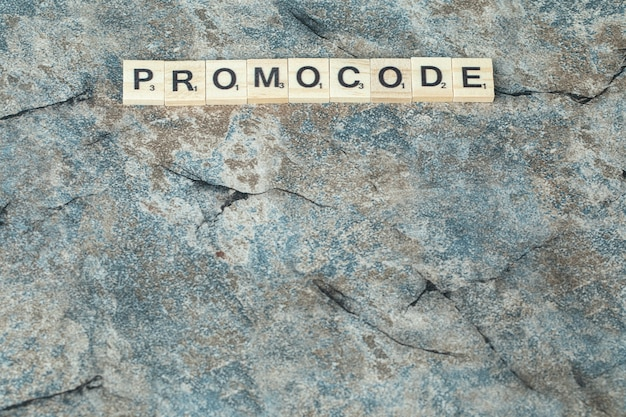 Promocode escrito con letras negras en dados de madera sobre el hormigón