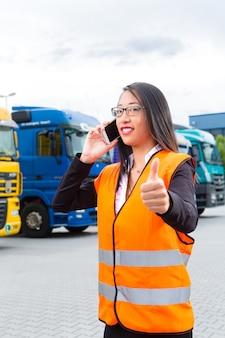 Promotor femenino frente a camiones en un depósito
