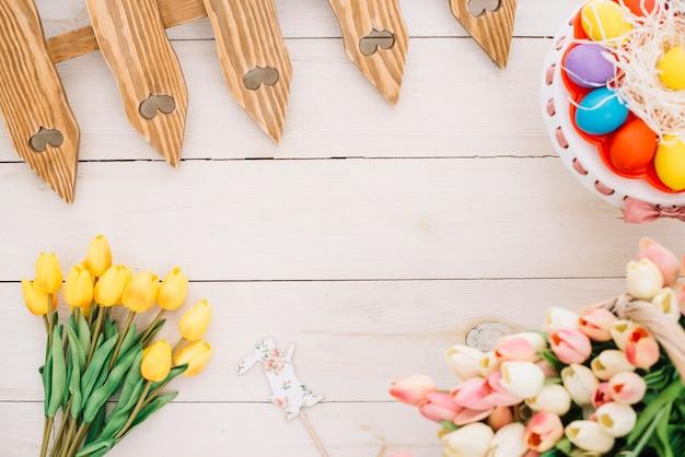 Prop pascua; tulipanes huevos de pascua; tulipanes y valla en escritorio de madera