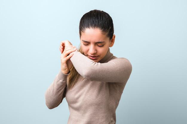 La propagación del coronavirus. mujer enferma con gripe o virus estornudando en el codo. protección antivirus incorrecta