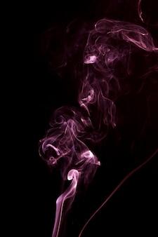 Propagación de humo rosa sobre el fondo negro.