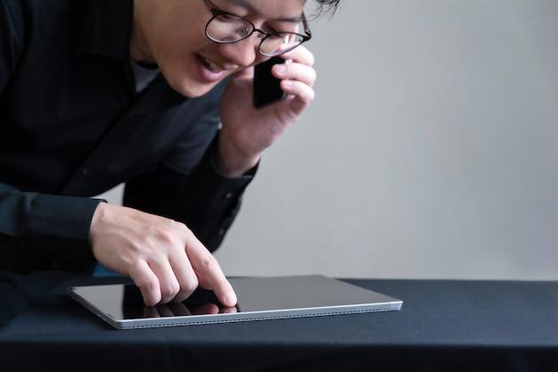 Propietario de empresa ocupado utilizando teléfonos inteligentes y tabletas digitales haciendo comercio electrónico, negocios en línea con concepto de tecnología inteligente