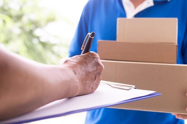 El propietario está firmando para recibir el paquete