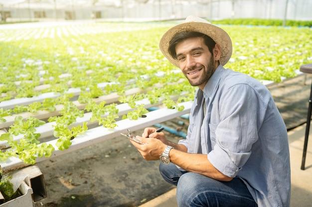 Propietario de una granja de hortalizas ver producción y control de calidad de la producción y crecimiento de hortalizas orgánicas