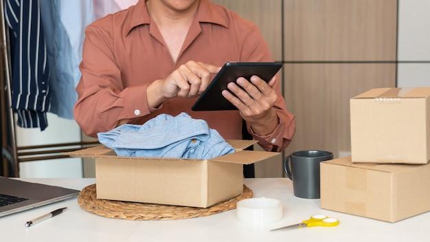 El propietario de un negocio asiático que trabaja en casa con la caja de embalaje de su tienda en línea se prepara para entregar productos a los clientes, concepto de estilo de vida de generación alfa.