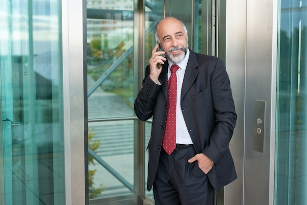 Propietario de negocio maduro seguro positivo hablando por celular
