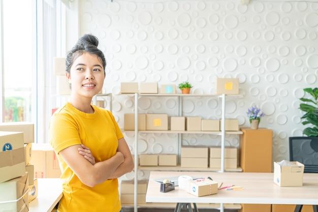 Propietario de negocio de mujeres asiáticas que trabaja en casa con caja de embalaje en el lugar de trabajo - empresario de pyme de compras en línea o concepto de trabajo independiente