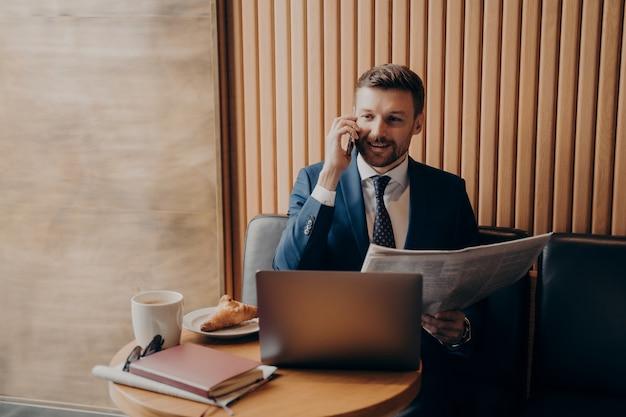 Propietario de negocio satisfecho con traje azul hablando por teléfono con el periódico en la mano, compartiendo noticias recientes con su socio y mirando la computadora portátil, notificando sobre nuevos desarrollos mientras trabaja en la cafetería