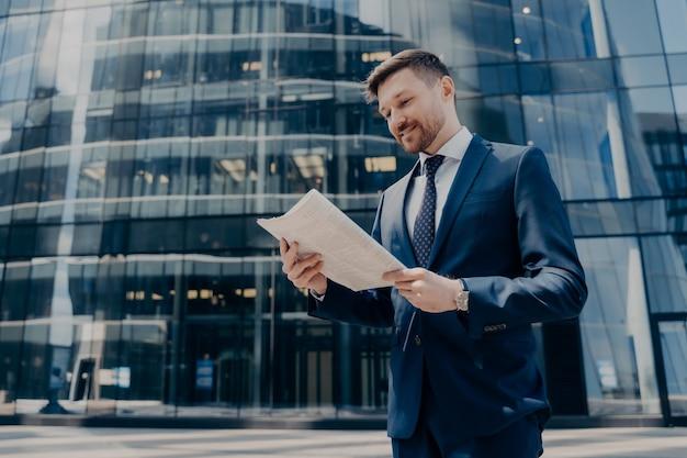 Propietario de negocio sonriente exitoso en traje azul leyendo buenas noticias en el periódico y sonriendo mientras está parado afuera solo con un edificio de oficinas de vidrio detrás de él, caminando durante las vacaciones al aire libre