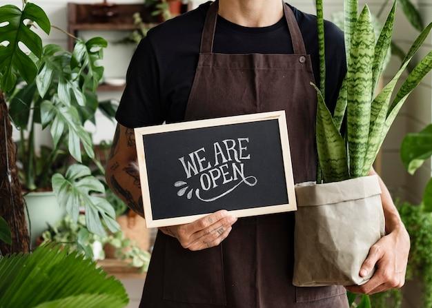 Propietario de negocio sosteniendo estamos abiertos signo