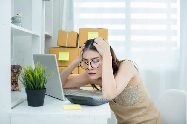 Propietario de negocio trabajando en la oficina de embalaje de la casa