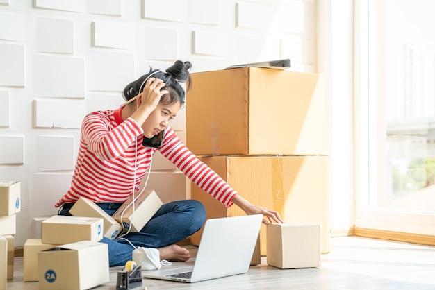 Propietario de negocios de mujeres asiáticas que trabajan en casa con caja de embalaje en el lugar de trabajo - empresario de pyme de compras en línea o concepto de venta en línea