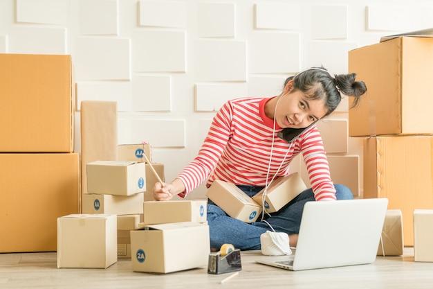 Propietario de negocios de mujeres asiáticas trabajando en casa con caja de embalaje en el lugar de trabajo