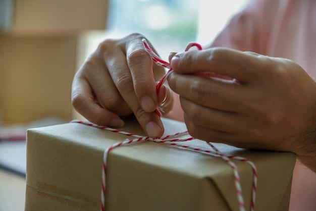 El propietario de una pequeña empresa asiática está utilizando la caja de cuerda de la cola para prepararse para la entrega al cliente.