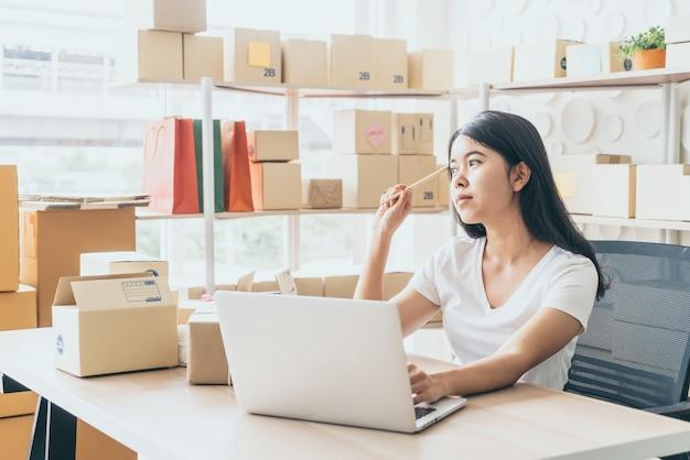 Propietario de pequeña empresa, mujer revisando orden de compra en laptop