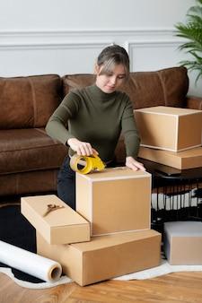 Propietario de una pequeña empresa que embala las cajas del paquete del producto para la entrega