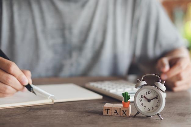 Propietario sentado en el cálculo del impuesto anual pulseras de la facturación para reducir el impuesto.