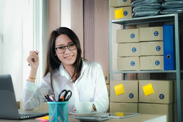 Propietario de la sme start up recibe órdenes de compra de clientes en línea con la computadora portátil