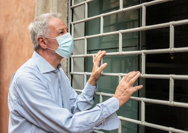 Propietario de una tienda desesperada frente a su negocio cerrado debido a la pandemia de coronavirus