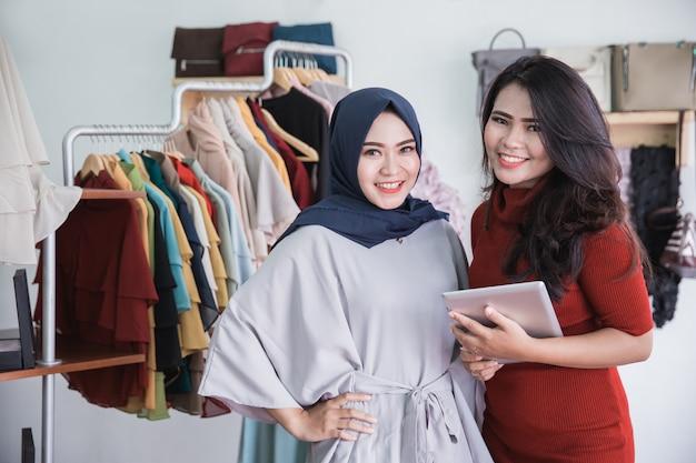 Propietario de tienda de moda y su asistente usando tableta en tienda de moda