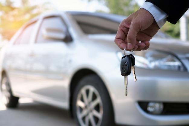 El propietario del vehículo está de pie las llaves del coche al comprador. venta de autos usados