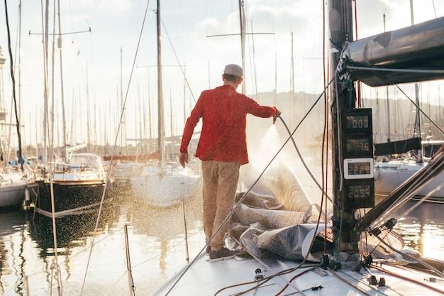 El propietario de un velero o un navegante utiliza una manguera para lavar el agua salada de la cubierta del yate cuando está atracado o estacionado en la marina al atardecer