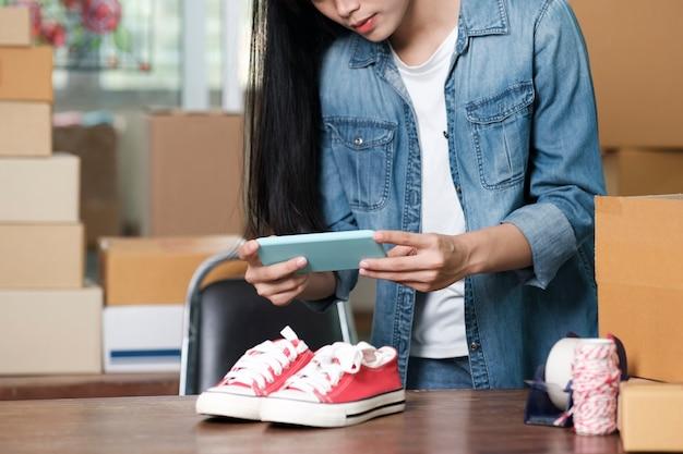El propietario del vendedor en línea toma una foto del producto para cargarla en la tienda en línea del sitio web. concepto de venta en línea, compras en línea y comercio electrónico.